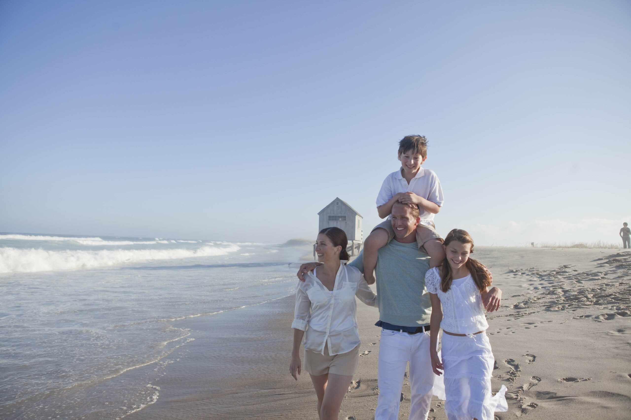Family of four walking on the beach.