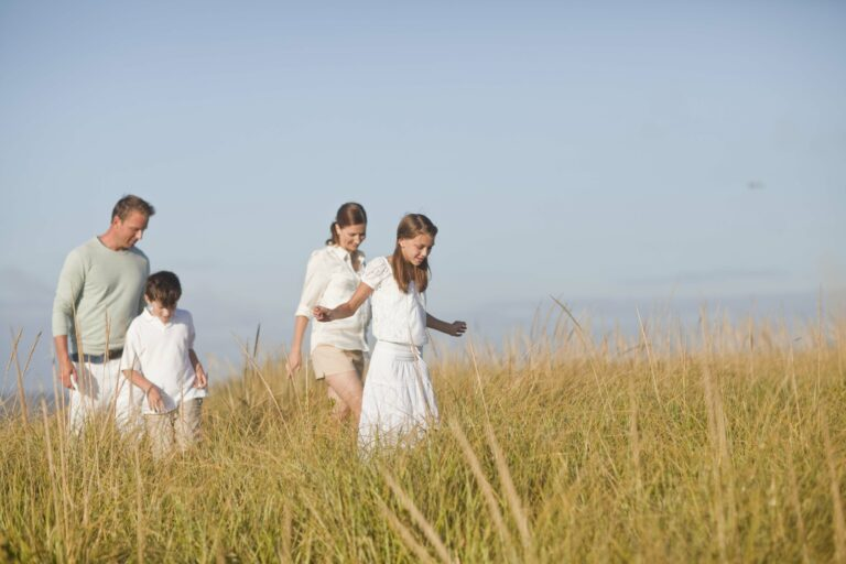 Family of four walking through a field of tall grass.