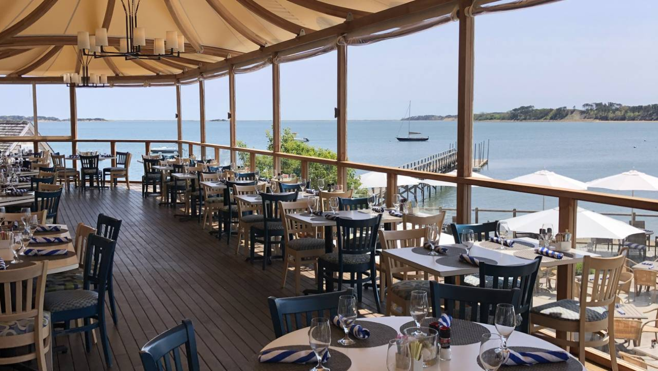 Wequassett Outer Bar & Grill outdoor dining tables overlooking bay