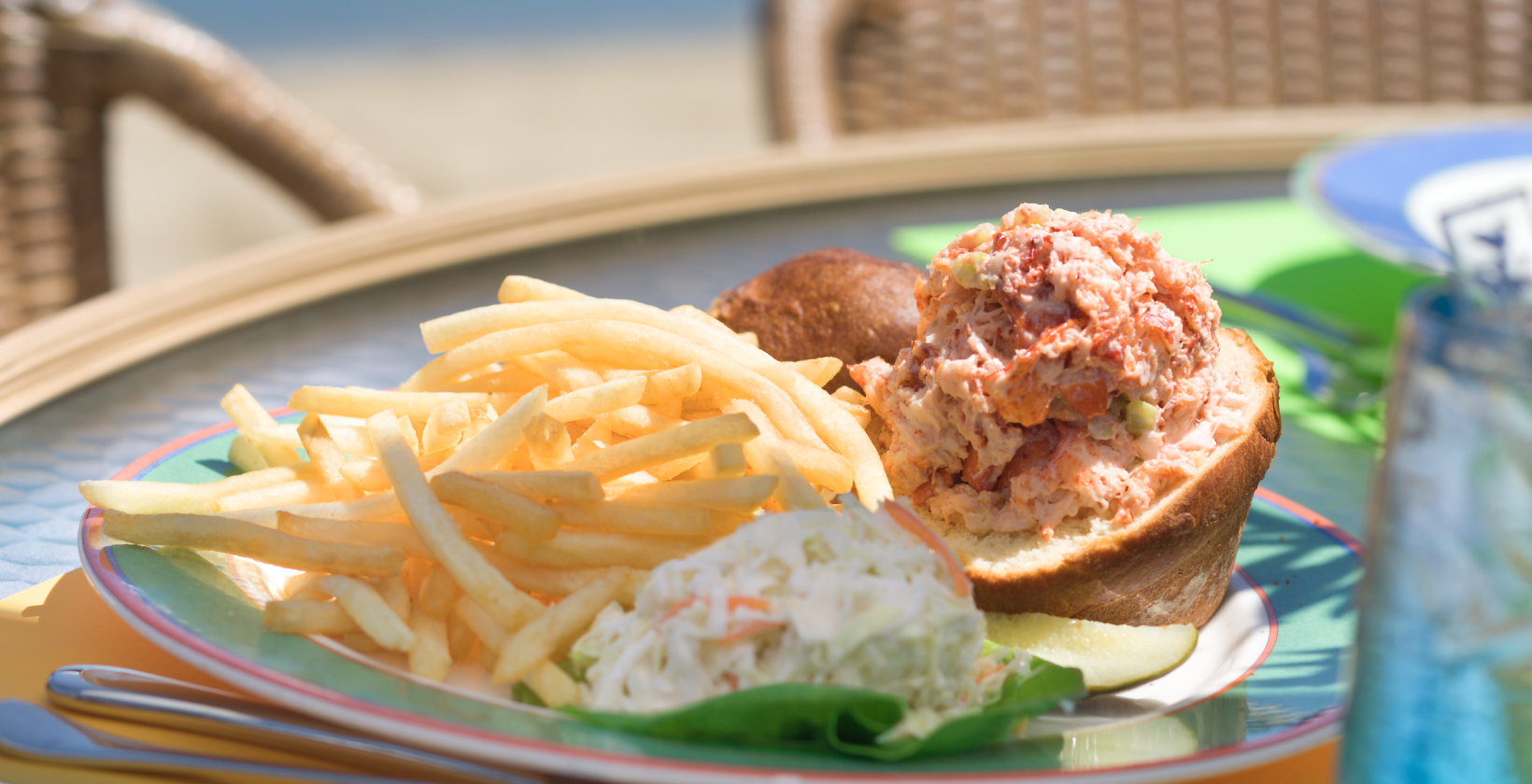lobster roll and fries on plate outdoor patio table