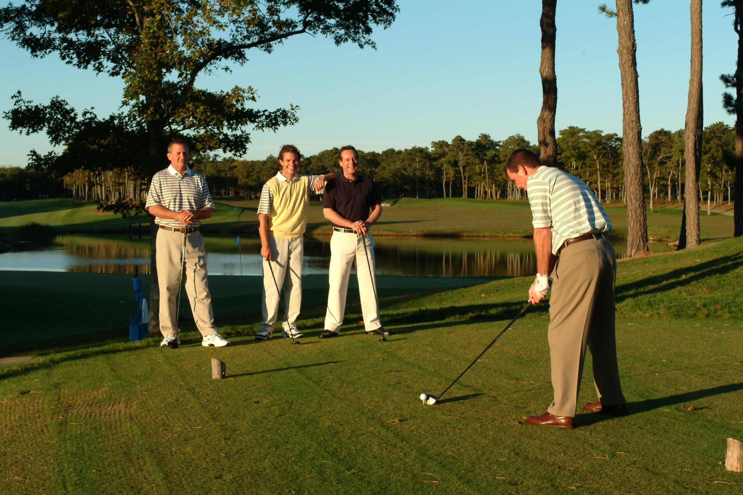 Four men playing golf.